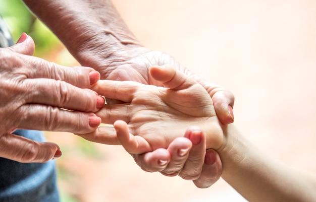 Hand einer älteren frau, die hand eines kindes anhält