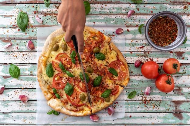 Hand einer frau, die ein stück pizza von oben auf rustikalen türkisfarbenen brettern betrachtet