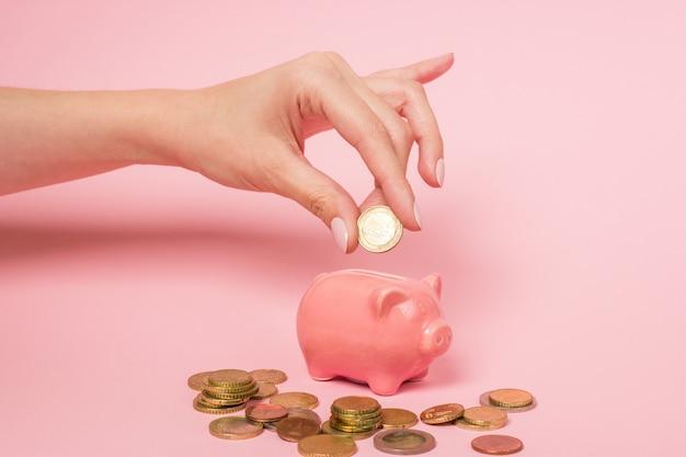 Hand einer frau, die eine euromünze in ein rosa keramisches sparschwein einfügt