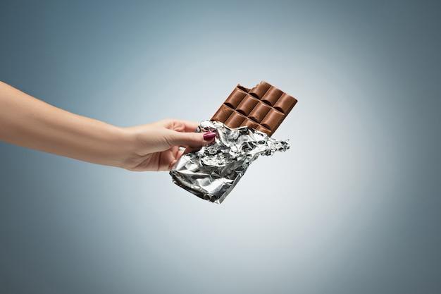 Hand einer frau, die eine fliese der schokolade anhält