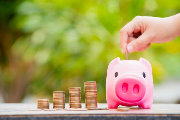 Hand einer frau, die eine münze in ein sparschwein steckt: geld für zukünftiges konzept sparen