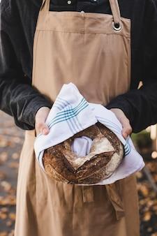 Hand einer frau, die großes bagelbrot eingewickelt in der weißen serviette hält
