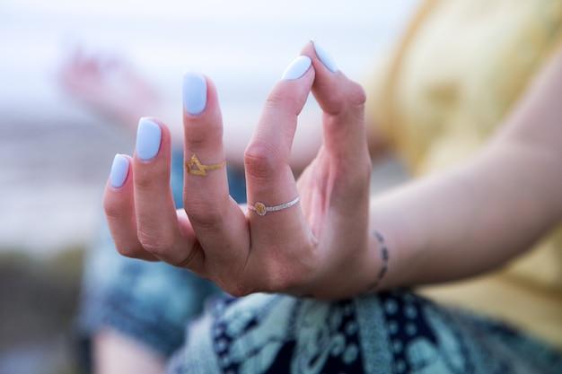 Hand einer frau, die in einer yogahaltung auf dem strand bei sonnenuntergang meditiert