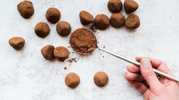 Hand einer frau, die kakaopulver im löffel auf weißem strukturiertem hintergrund hält