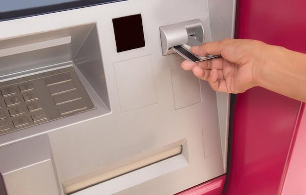 Hand einer frau mit einer kreditkarte, unter verwendung eines atms. frau mit einem geldautomaten.