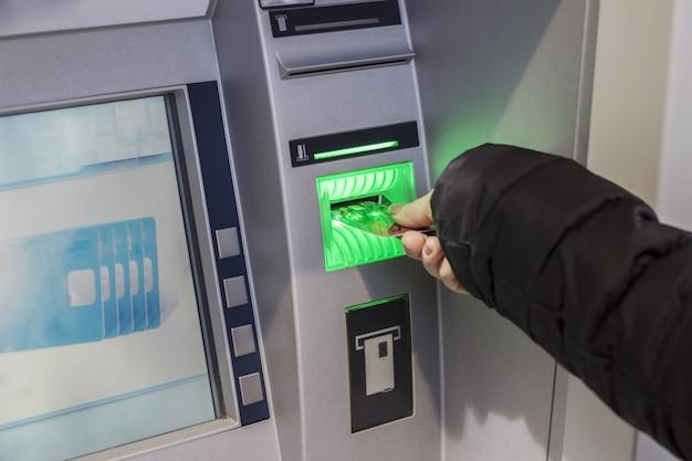 Hand einer frau mit einer kreditkarte, unter verwendung eines atms. frau mit einem