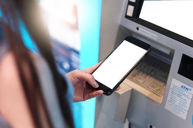 Hand einer frau mit einer kreditkarte, unter verwendung eines atms
