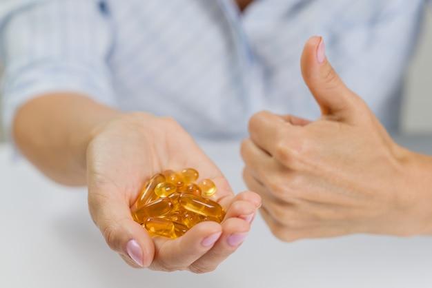 Hand einer frau mit fischöl omega-3-kapseln