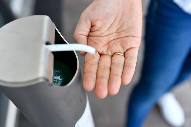 Hand einer jungen erwachsenen frau mit ehering, die desinfektionsmittel oder hydrogel auf ihre hände auf der straße aufträgt