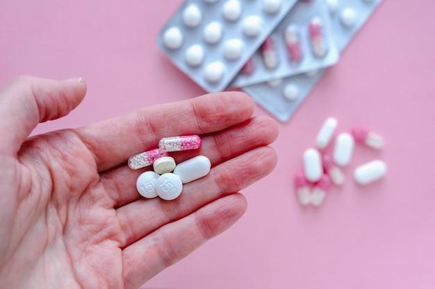 Hand einer jungen frau, die eine pille hält.