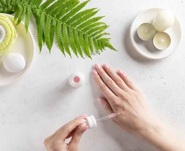 Hand einer jungen frau, die serum (kollagen-feuchtigkeitscreme, hyaluronsäure, vitamin c) auf die haut aufträgt. hautpflege routine. weiße wand mit kerzen und grünem blatt. draufsicht.