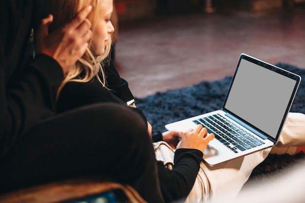 Hand einer jungen frau, die zu hause am laptop arbeitet, während sie auf dem boden sitzt und sich auf ihren freund stützt.