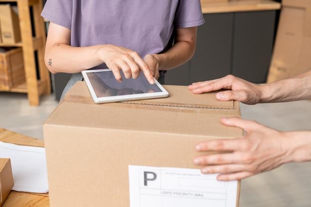 Hand einer jungen managerin des online-shops, die auf den bildschirm des digitalen tablets zeigt, während sie ihrem kollegen die bestell- oder artikelnummer zeigt
