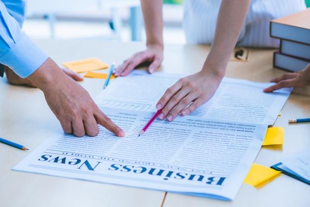Hand einer modernen unternehmensberater-sitzung, um die situation in der zeitung zu analysieren und zu diskutieren