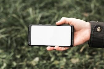 Hand einer Person, die den Handy zeigt weiße Anzeige des leeren Bildschirms an draußen hält