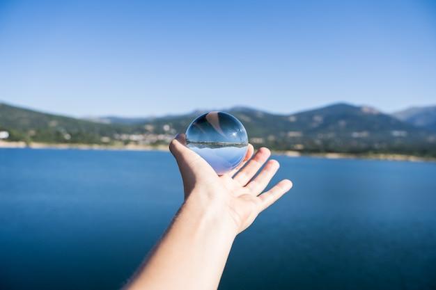 Hand einer person, die eine kristallkugel hält, die die landschaft eines sees mit bergen in einem wasserreservoir in navacerrada reflektiert