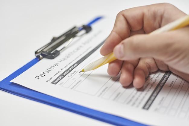 Hand einer person, die einen krankenversicherungsantrag ausfüllt