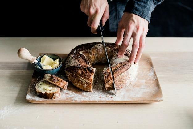 Hand einer person, die gebackenen bagel mit scharfem messer auf hackendem brett schneidet