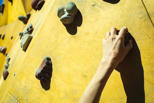 Hand einer person, die versucht, das fixie einer kletterwand zu klettern