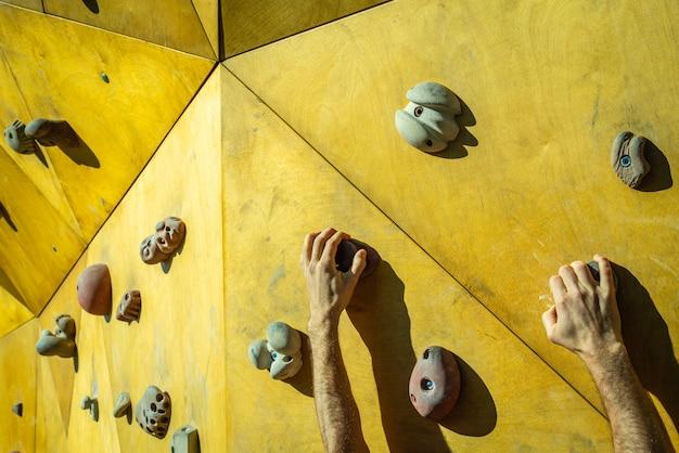 Hand einer person, die versucht, den fixie einer kletterwand zu besteigen