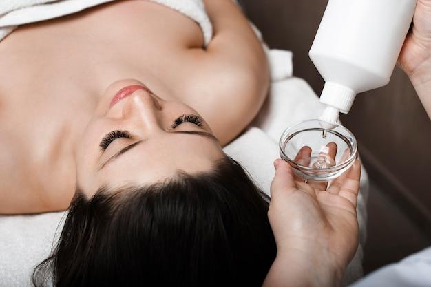 Hand einer weiblichen kosmetikerin, die eine transparente maske in eine schüssel setzt, während in der nähe auf einem spa-bett eine junge frau lehnt, die mit geschlossenen augen auf gesichtsmaske wartet.