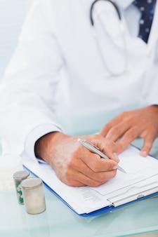 Hand eines Doktors schreiben auf einer Verordnungsauflage