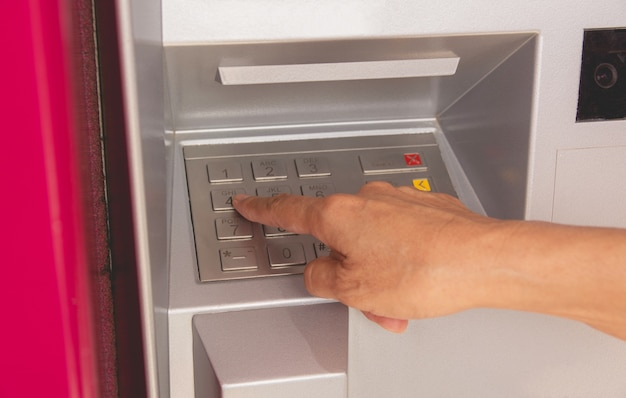 Hand eines frauendruckknopfes in atm, unter verwendung eines atms. frau mit einem geldautomaten.