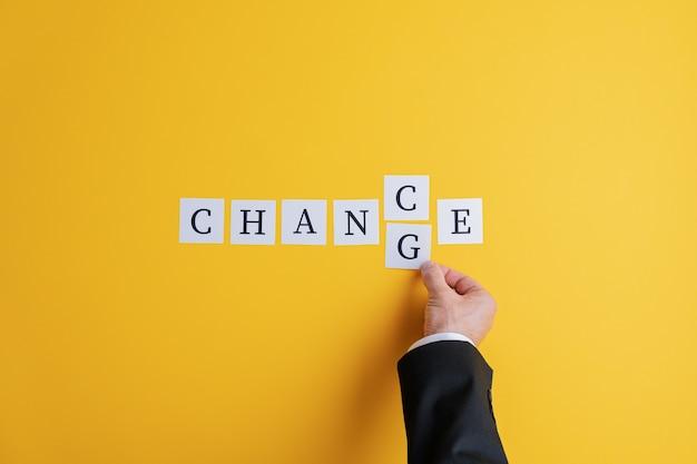 Hand eines geschäftsmannes, der das wort chance in veränderung ändert, geschrieben auf post-it-papier.