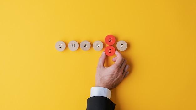 Hand eines geschäftsmannes, der die buchstaben g und c ändert, um ein änderungszeichen in zufall umzuwandeln, der auf hölzernen geschnittenen kreisen geschrieben wird.