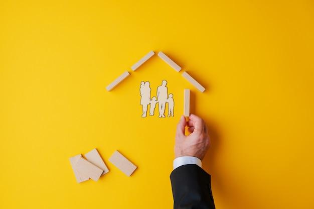 Hand eines geschäftsmannes, der ein haus der hölzernen heringe um eine papierschnittschattenbild einer familie in einem konzeptuellen bild von versicherung und immobilien macht.