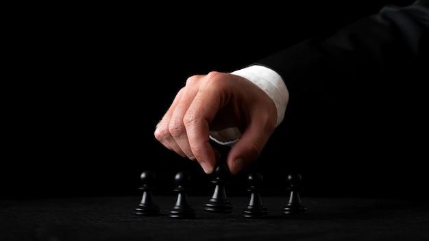 Hand eines geschäftsmannes, der schachfiguren in einem konzeptionellen bild von führung und macht anordnet. auf schwarzem hintergrund.
