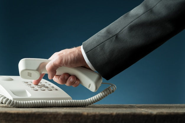 Hand eines geschäftsmannes, der telefonhörer hält, der telefonnummer wählt