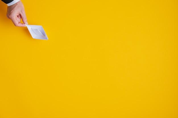 Hand eines geschäftsmannes, der weißes papier machte, machte origami-boot auf der linken oberen ecke des bildes. über gelbem hintergrund mit viel kopierraum.