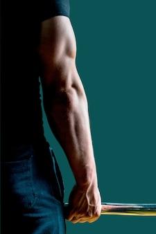 Hand eines jungen hübschen trainers der muskulösen eignung nah oben mit einem gewicht.