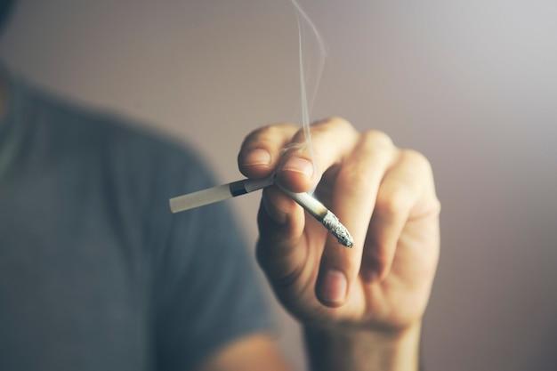 Hand eines jungen kaukasischen mannes, der eine brennende zigarette mit seinen fingern bricht