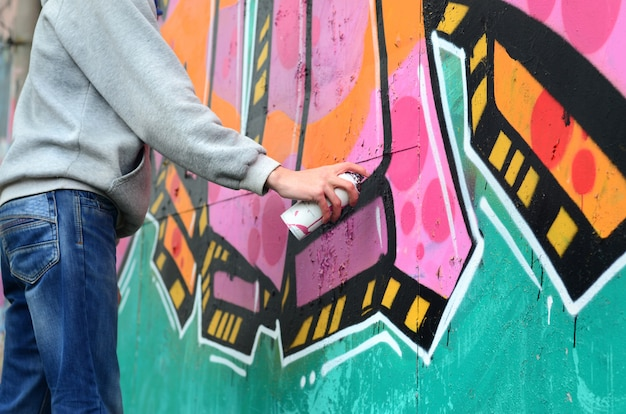 Hand eines jungen kerls in einem grauen hoodie malt graffiti