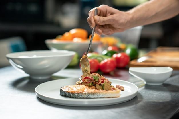 Hand eines jungen männlichen kochs, der gebratenes gemüse auf ein stück gebratenen lachs auf den teller legt, während er leckeres essen für den kunden des restaurants zubereitet