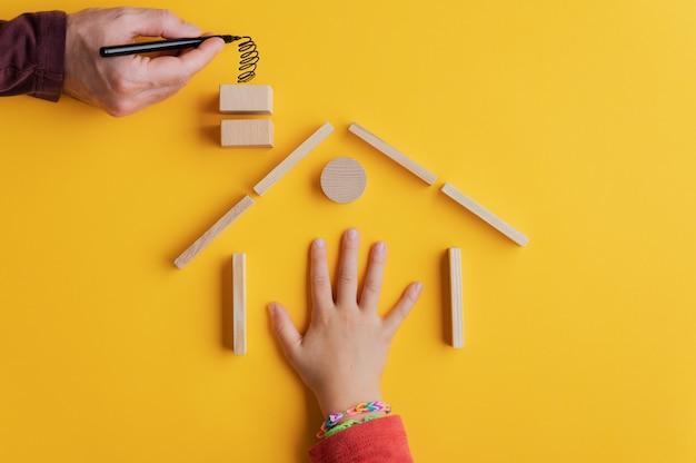 Hand eines kindes in einem haus, das von holzstiften und -blöcken mit männlicher hand gebaut wird, die rauch zieht, der aus dem schornstein in einem konzeptuellen bild des wohneigentums kommt. über gelbem hintergrund.