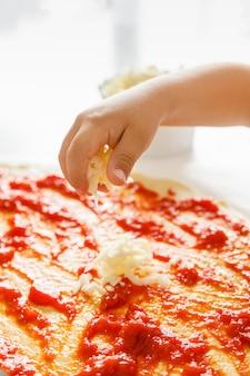 Hand eines kleinen kindes, das geriebenen käse auf eine pizza wirft