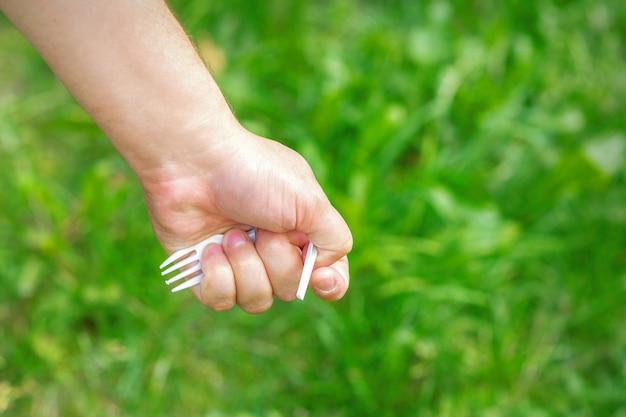 Hand eines kleinen mädchens, das plastikmüll auf grünem gras im park hält