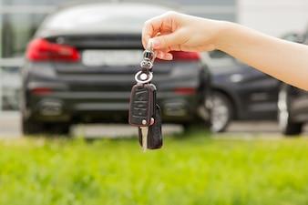 Hand eines Mädchens mit einem Autoschlüssel in ihrer Hand, gegen einen Neuwagenhintergrund