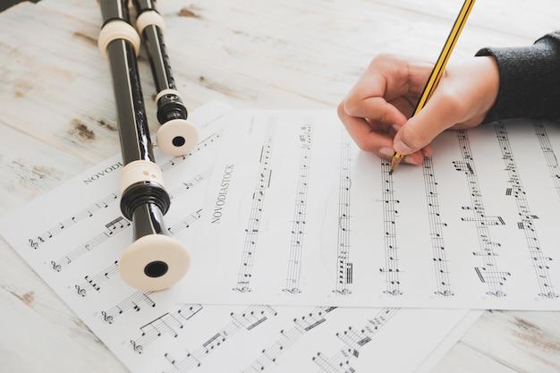 Hand eines mädchens, das musik auf papier schreibt