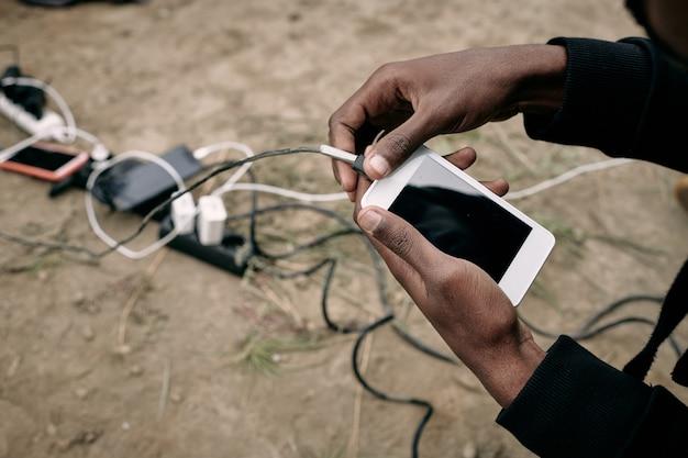 Hand eines männlichen migranten, der smartphone beim anrufen verbirgt