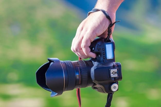 Hand eines mannes, der berufsdigitalkamera auf unscharfer grüner oberfläche hält