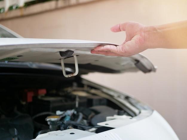 Hand eines mannes, der die motorhaube öffnet zur überprüfung des allgemeinen fahrzeugzustands motor, öl, kühler.