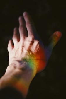 Hand eines mannes mit einer regenbogenbeschaffenheit auf der seite
