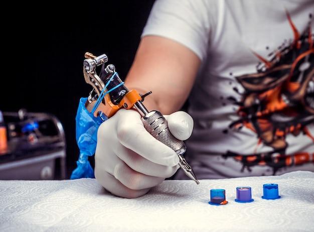 Hand eines meisters der tätowierungskunst und einer tätowiermaschine.