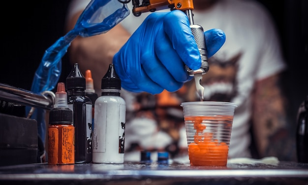 Hand eines meisters der tätowierungskunst und einer tätowierpistole