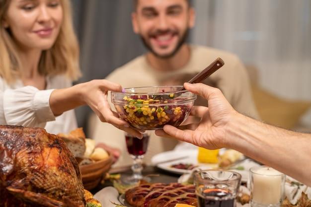 Hand eines reifen mannes, der eine schüssel mit frischem hausgemachtem salat an eine junge glückliche blonde frau weitergibt, die an einem servierten festlichen tisch neben ihrem ehemann sitzt?