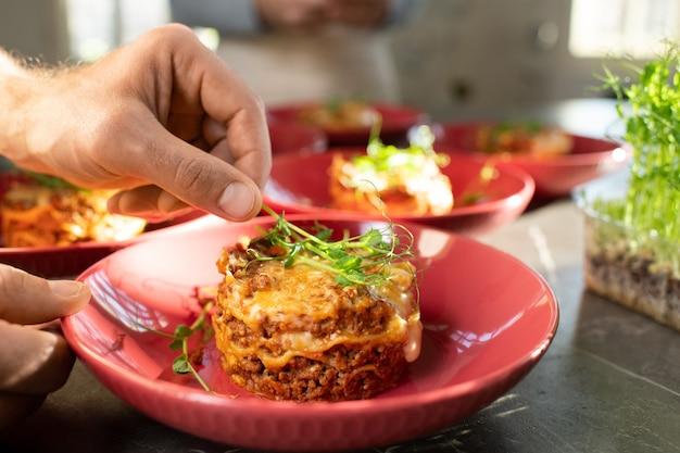 Hand eines reifen mannes, der einen zweig des frischen grünen dekorativen soja-sämlings auf ein appetitliches hausgemachtes fleischgericht auf einem roten porzellanteller legt